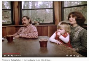 Set in the 1980's, Bill and Bette Byrne are sitting at a table with their two year old daughter on their lap. There are two brown coffee mugs on the table.