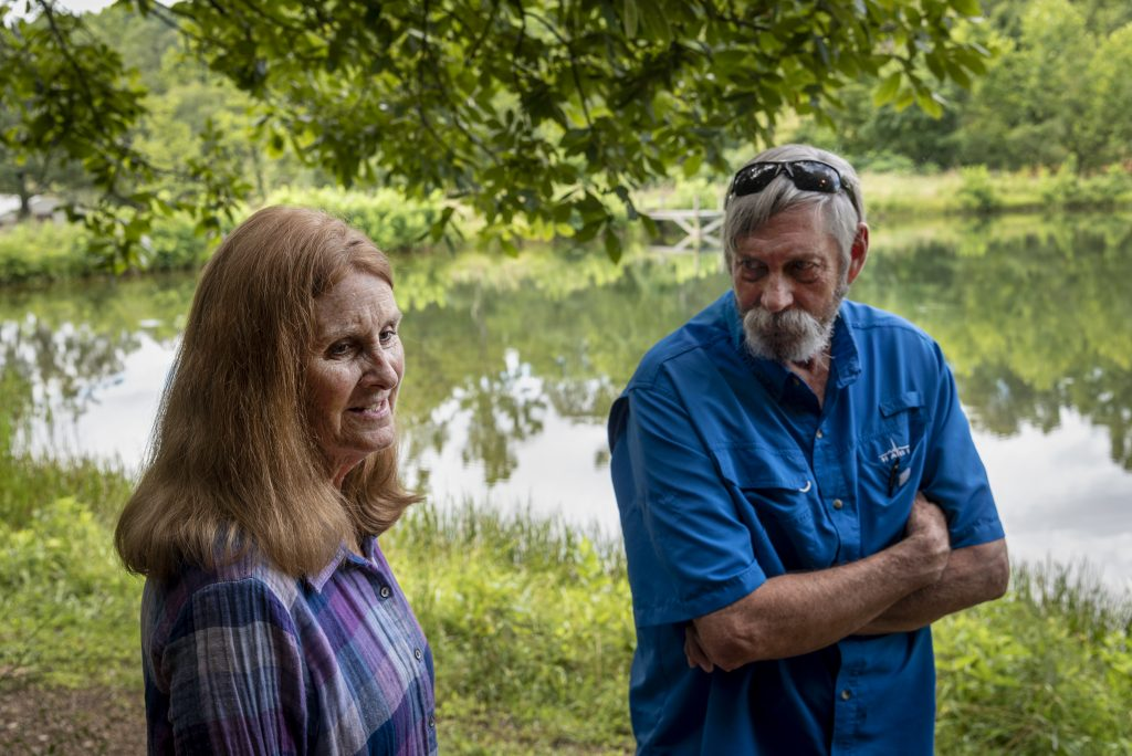 Bill and Bette Byrnes of today are standing by a pond. Bill is looking at Bette, she is smiling.